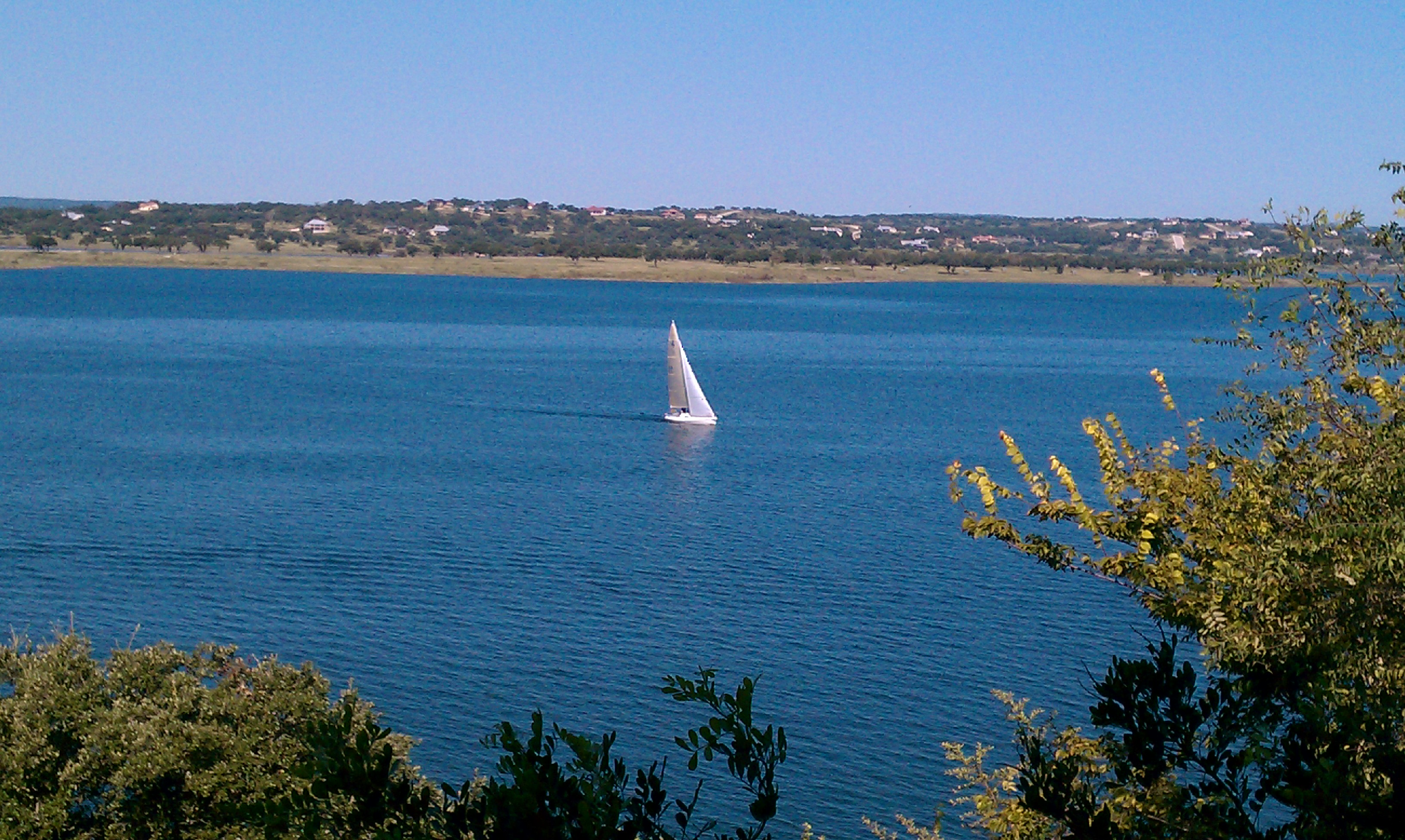Solitary Sailboat Blue Water And Sky